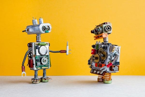 One robot handing a screwdriver tool to another robot