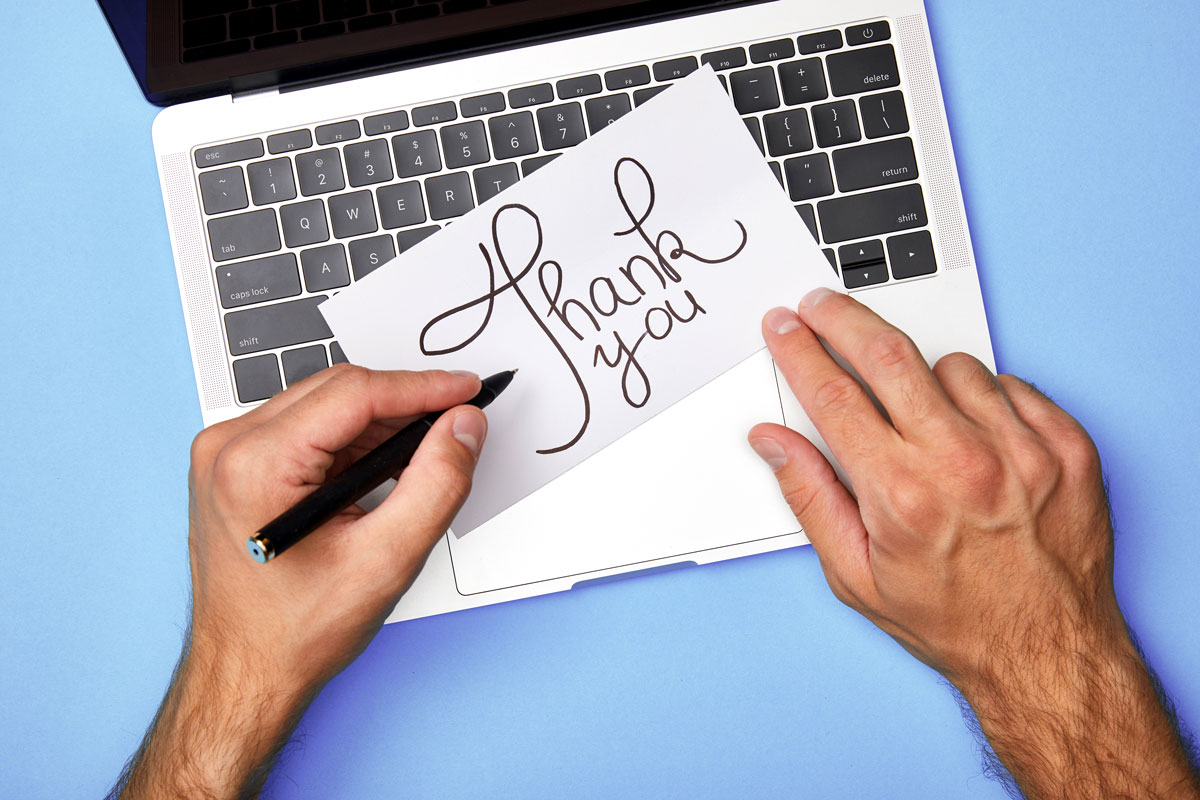A laptop and hands over it writing a thank you note for a work anniversary