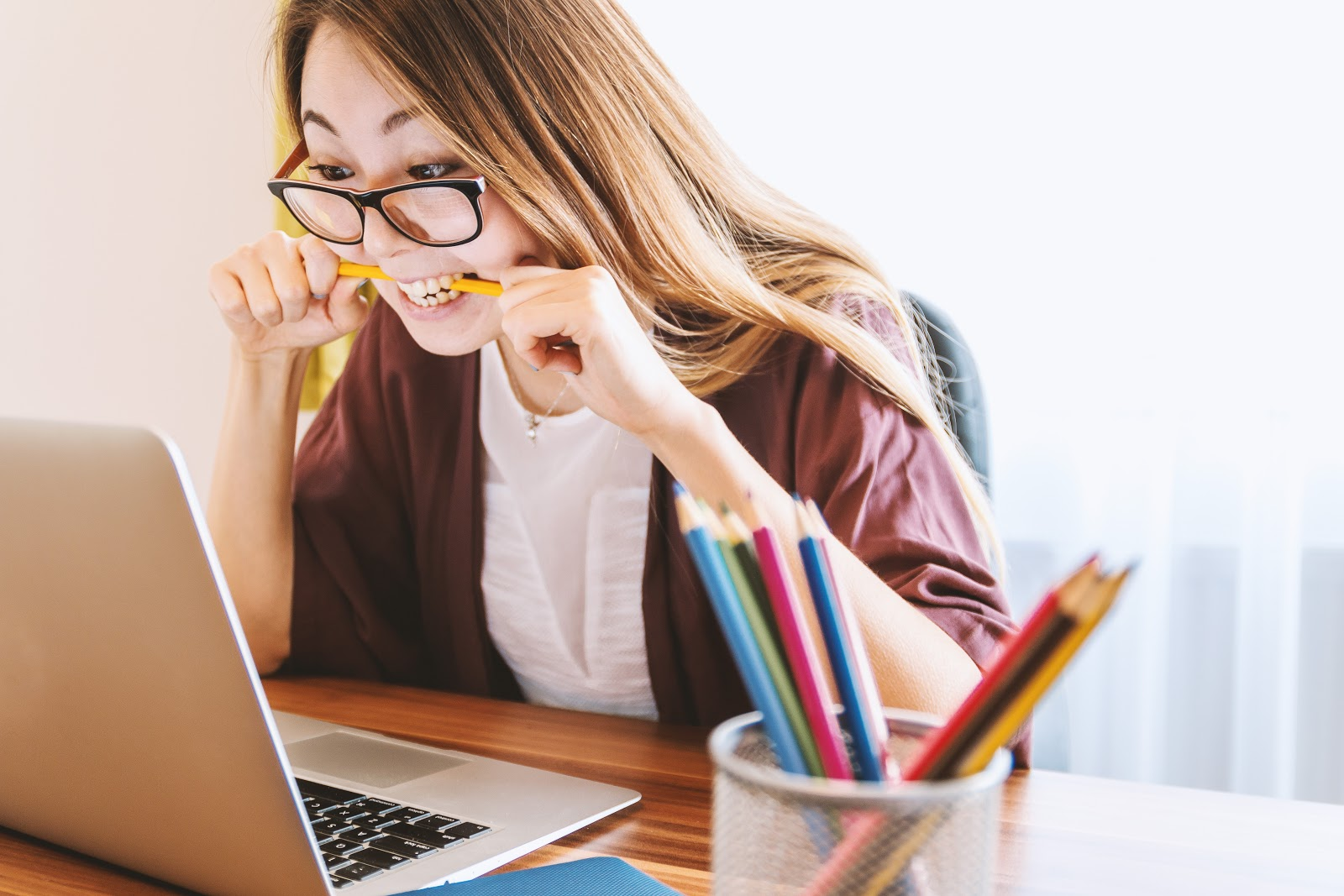 Woman in glasses sitting at a desk and biting a pencil while looking at the screen.
