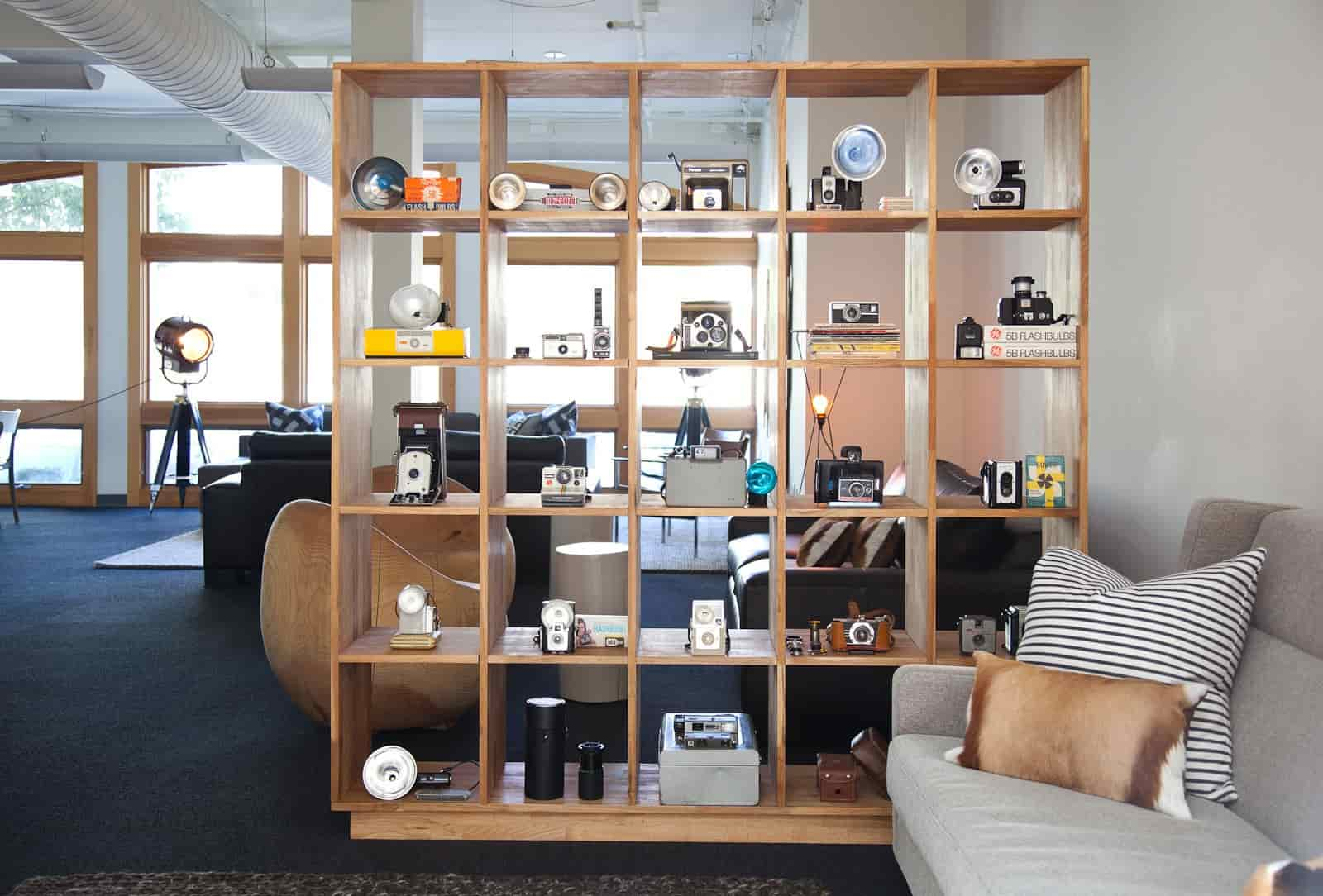 A comfortable and cozy office space with a couch and self with old vintage cameras