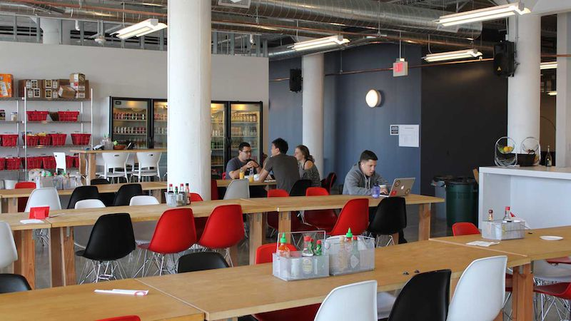 Office kitchen environment with long cafeteria style tables with a group of employees in the backgorunfd