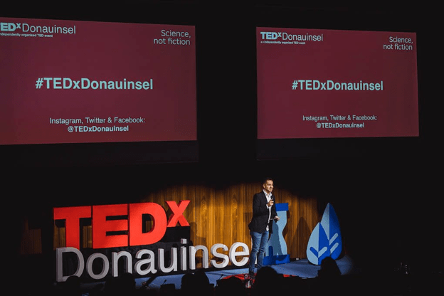 A photo of a TedX event displaying the event hastag on screens to boost brand recall