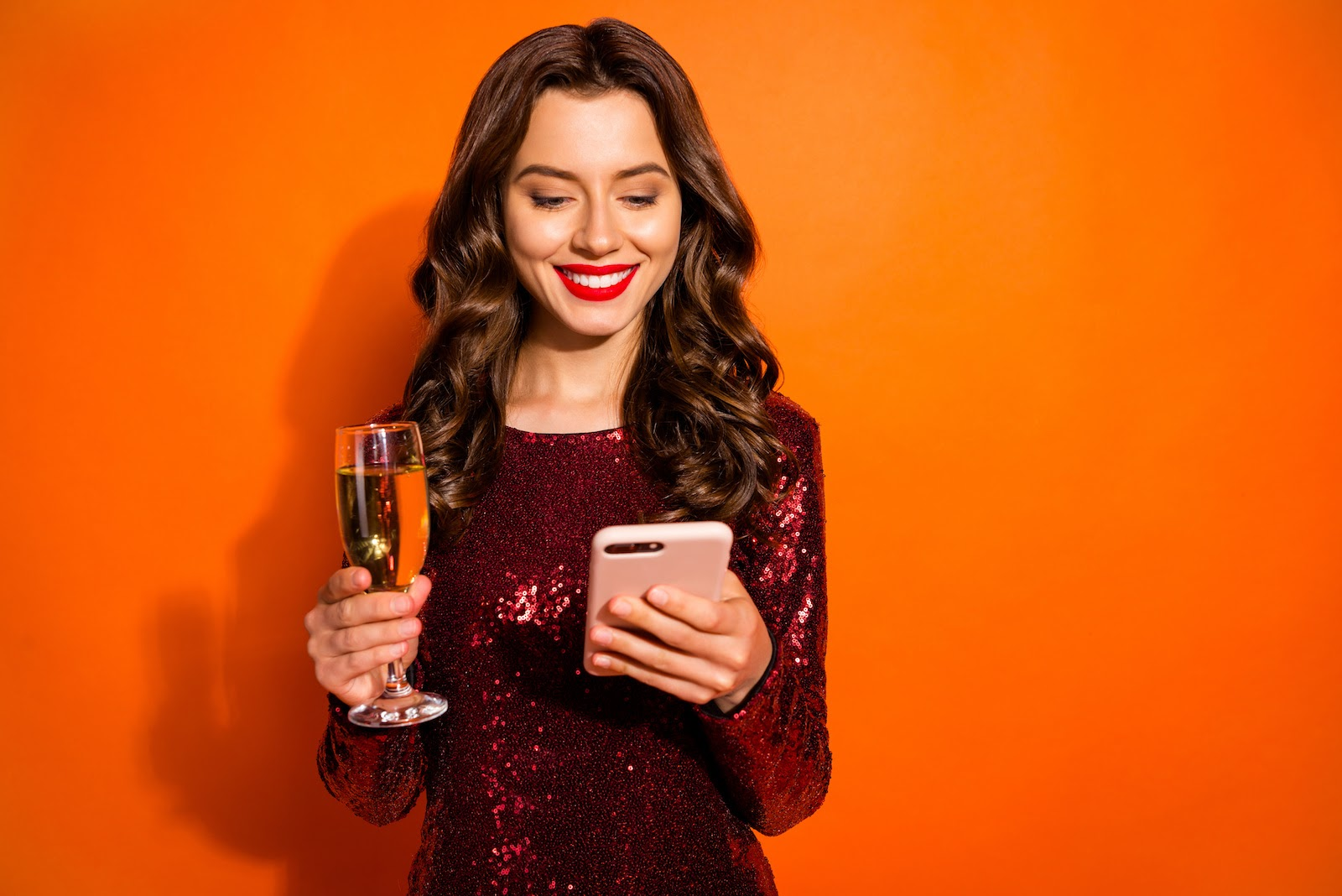 A woman holds champagne, wears a party dress, and looks at her phone for a virtual party