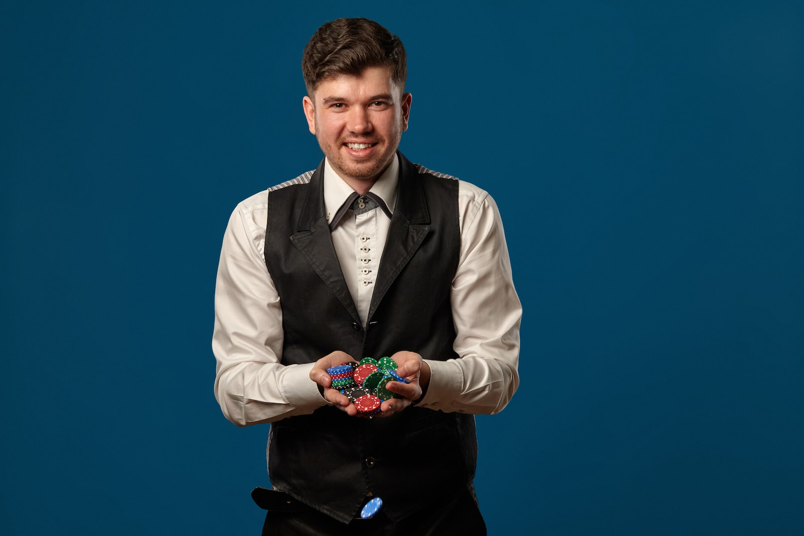 Virtual event ideas: A man holds poker chips, representing a virtual casino night