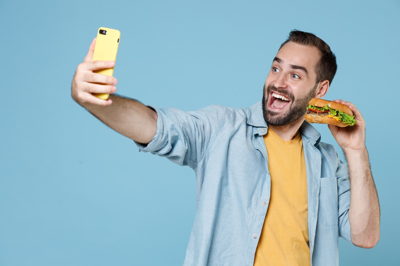 A man holds a burger and looks into his phone screen for a virtual lunch and learn