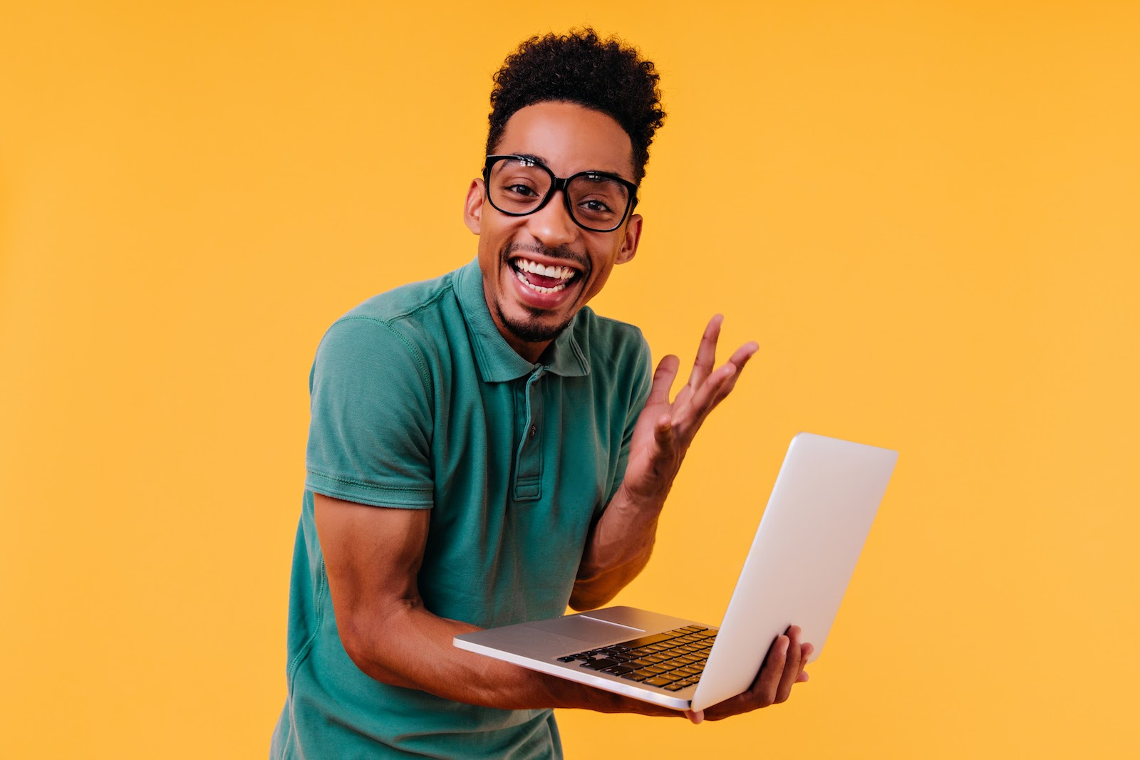 A man holds his laptop and looks excited