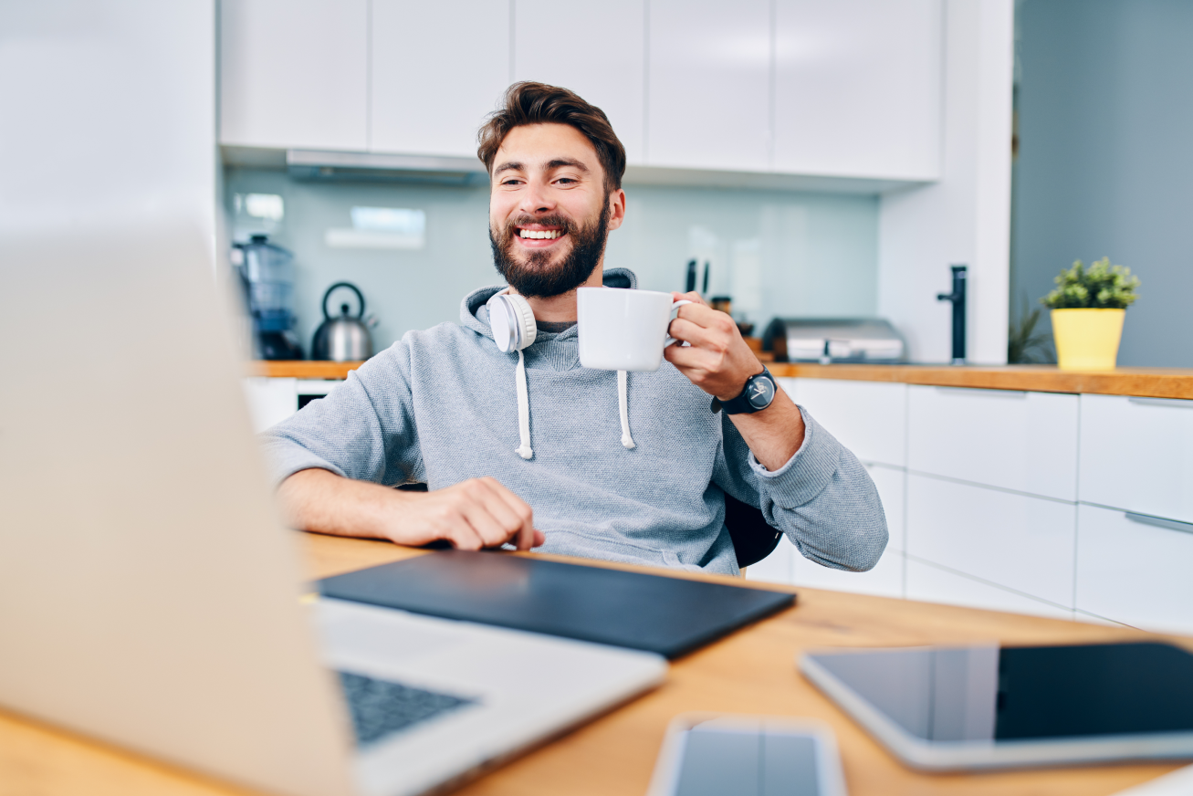 A man drinks coffee in front of his computer during a virtual meeting