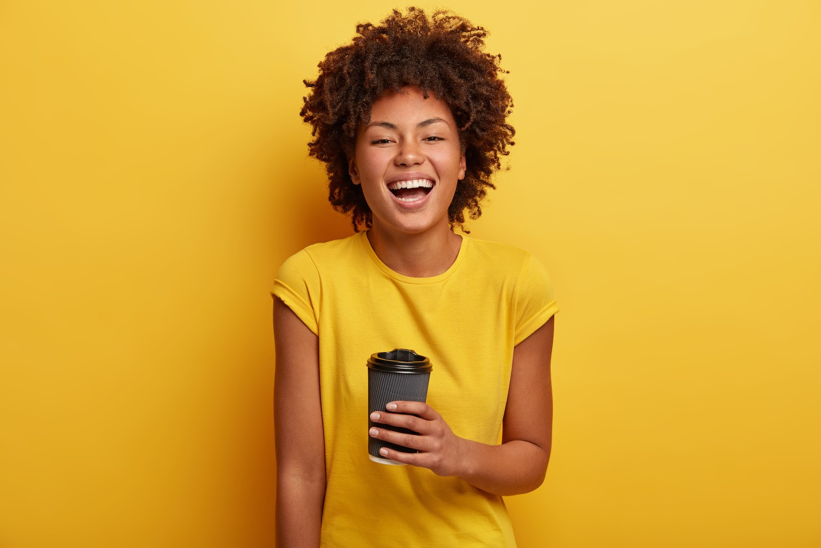 A woman holds a cup of coffee representing a virtual coffee event experience