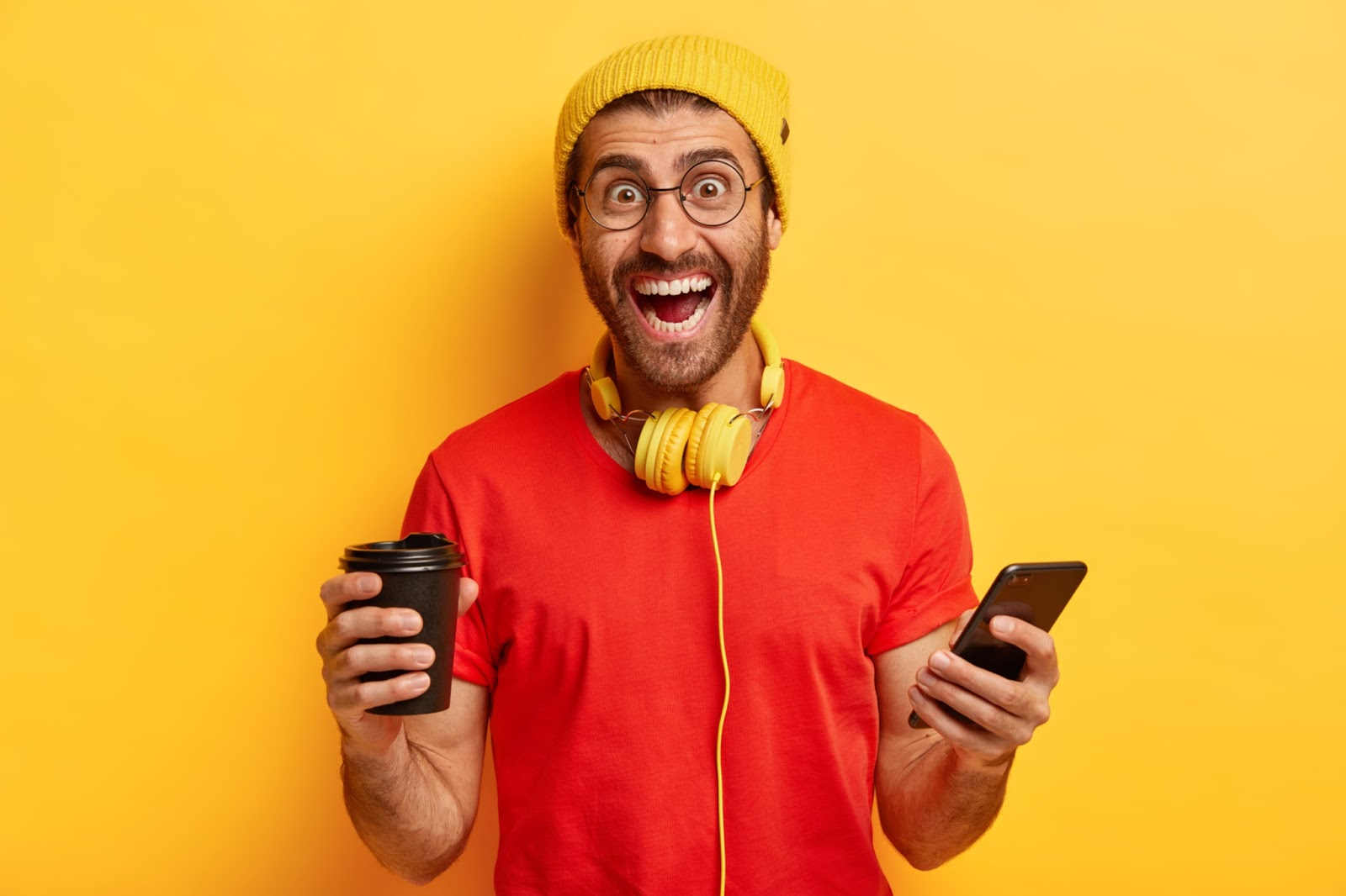 A man looks excited to attend virtual conferences with his phone, headphones, and a cup of coffee