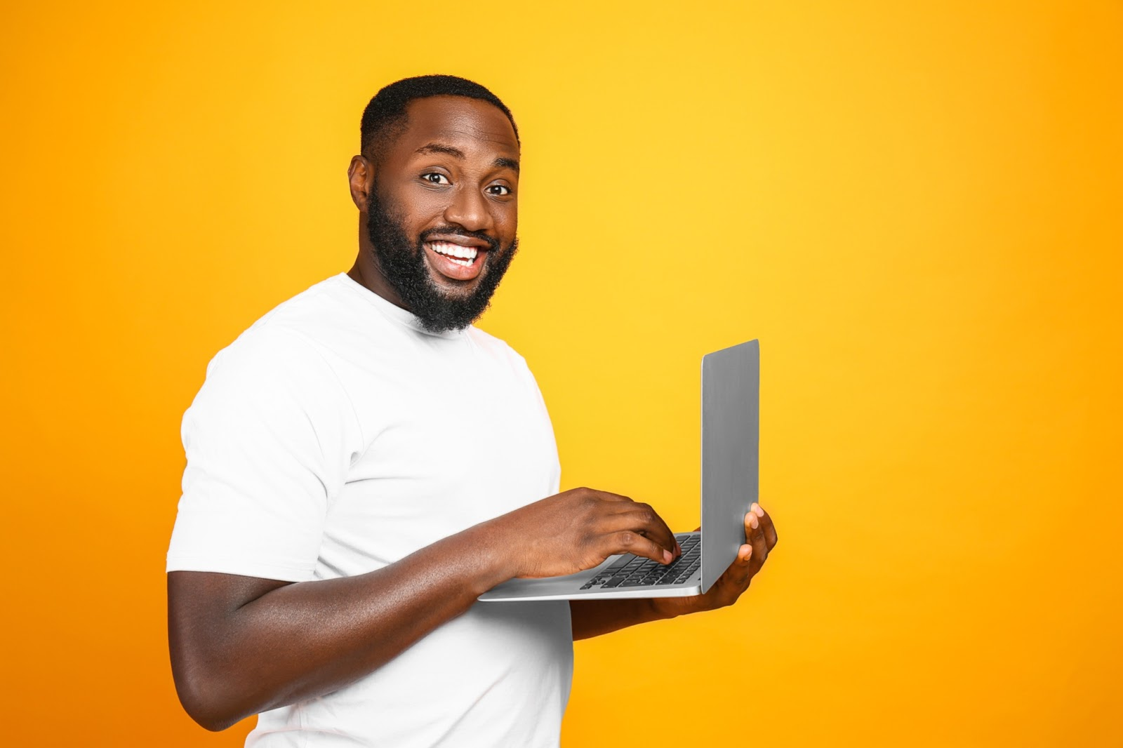 A smiling man works on a laptop