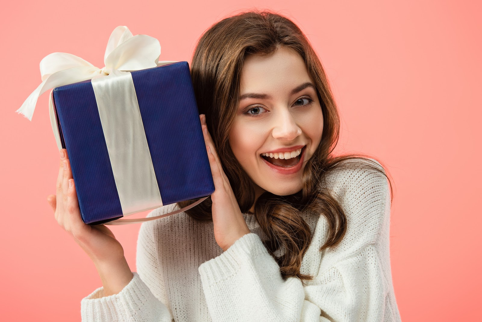 A virtual holiday party guests holds up a wrapped gift from a Secret Santa gift exchange