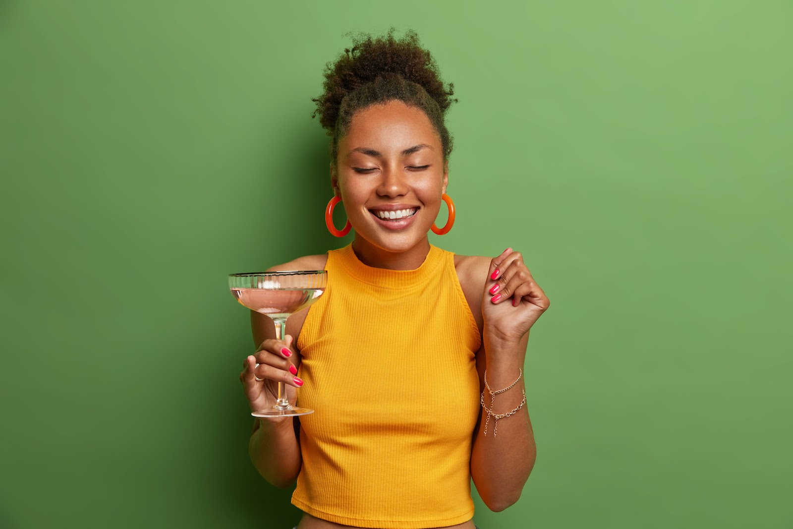 A virtual holiday party guest holds a festive cocktail