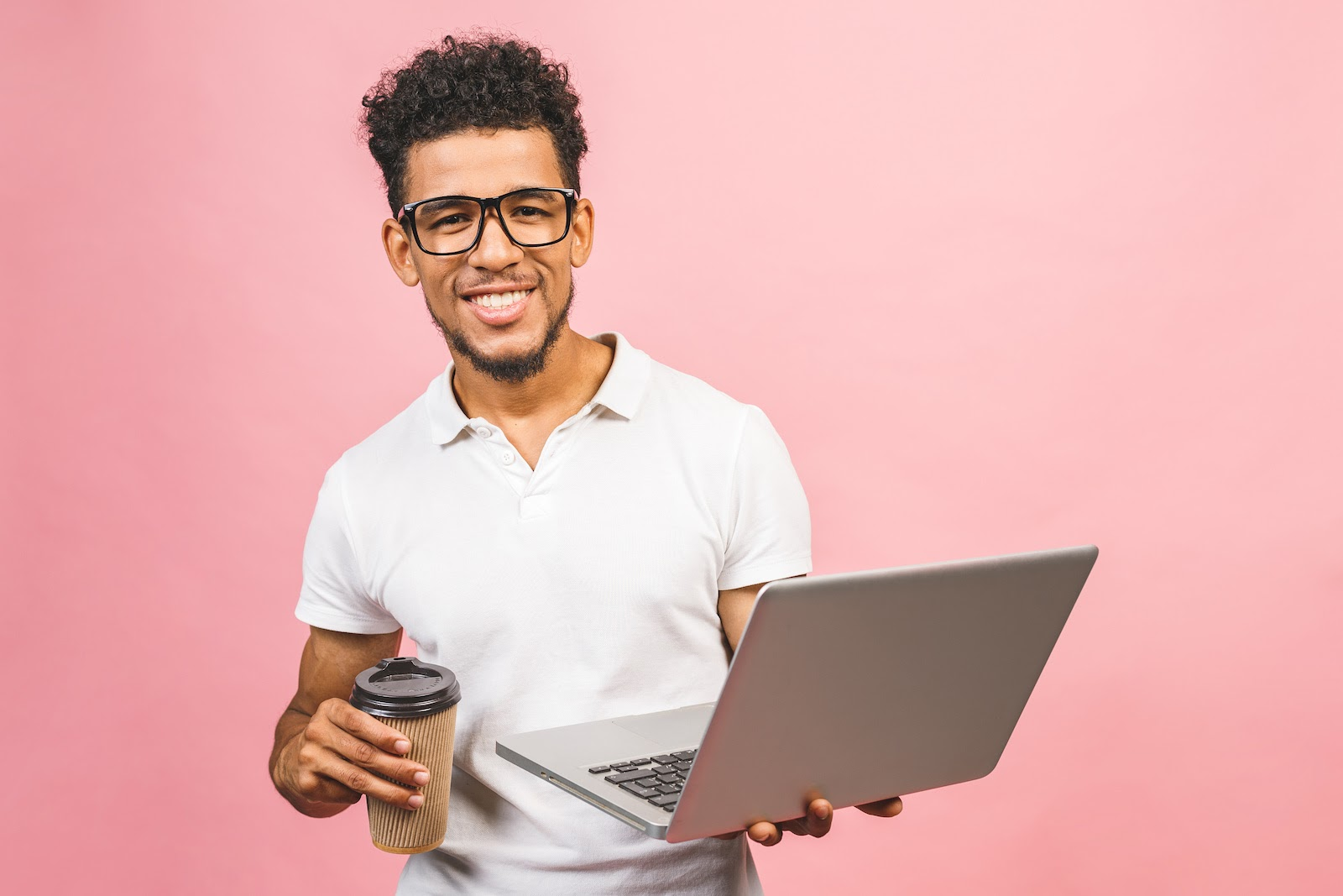 A man holds a laptop and coffee cup for a virtual coffee meeting