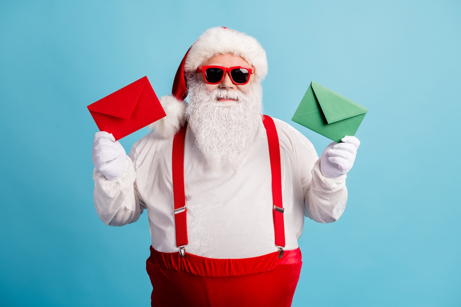 Santa Claus holds up two Christmas cards