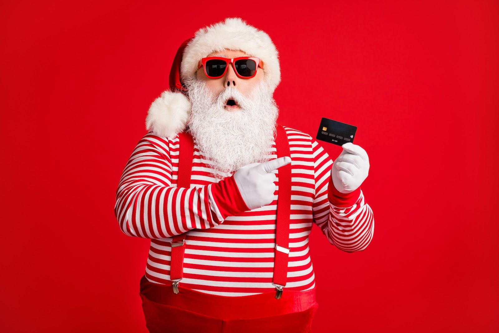Santa Claus holds a virtual credit card