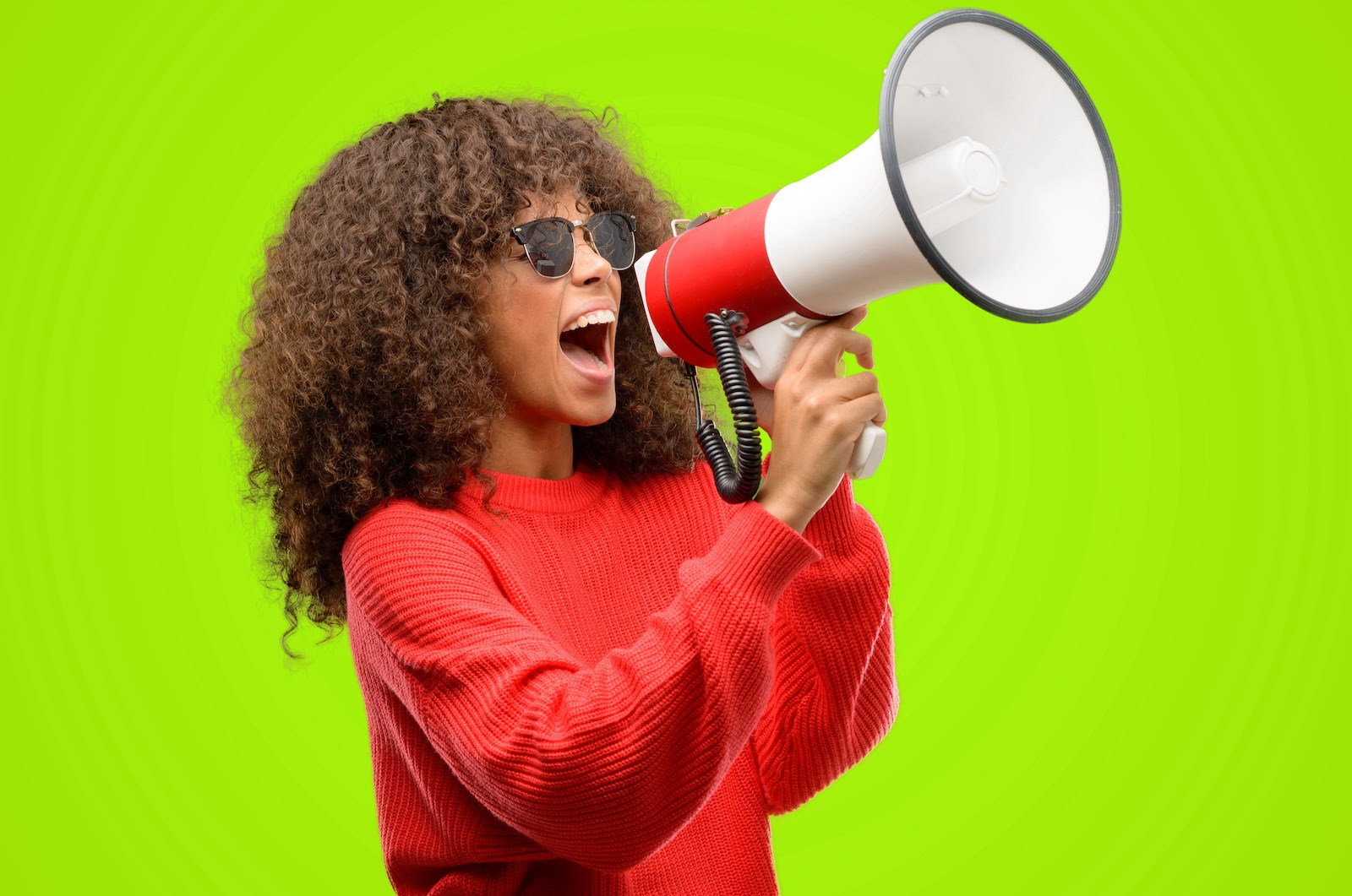 A woman talks into a megaphone to represent communication at a kickoff meeting
