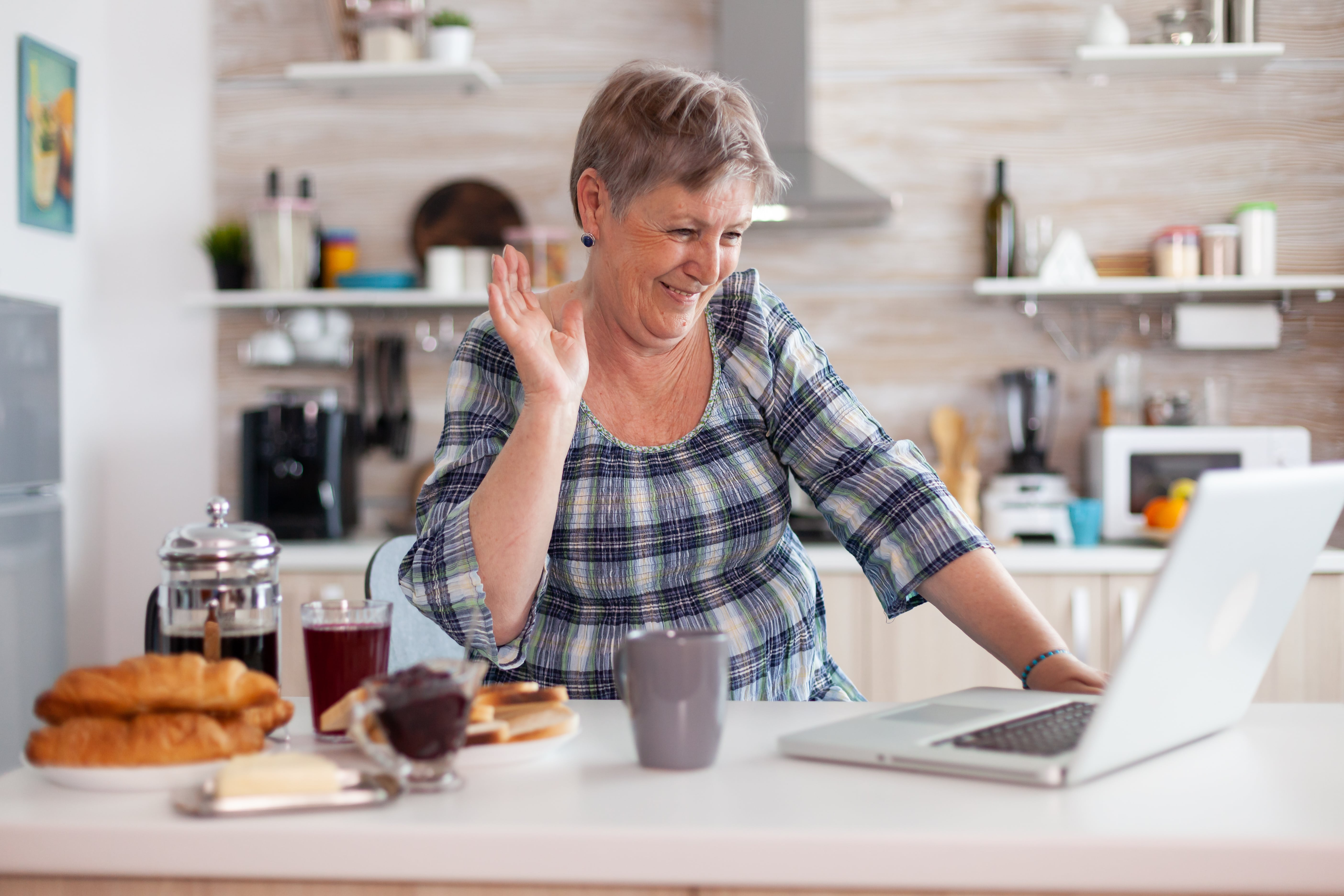 A woman waves at the camera on her laptop