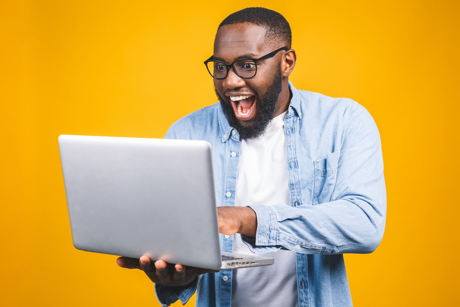 A man is excited about sales incentives for customers that he's received on his laptop