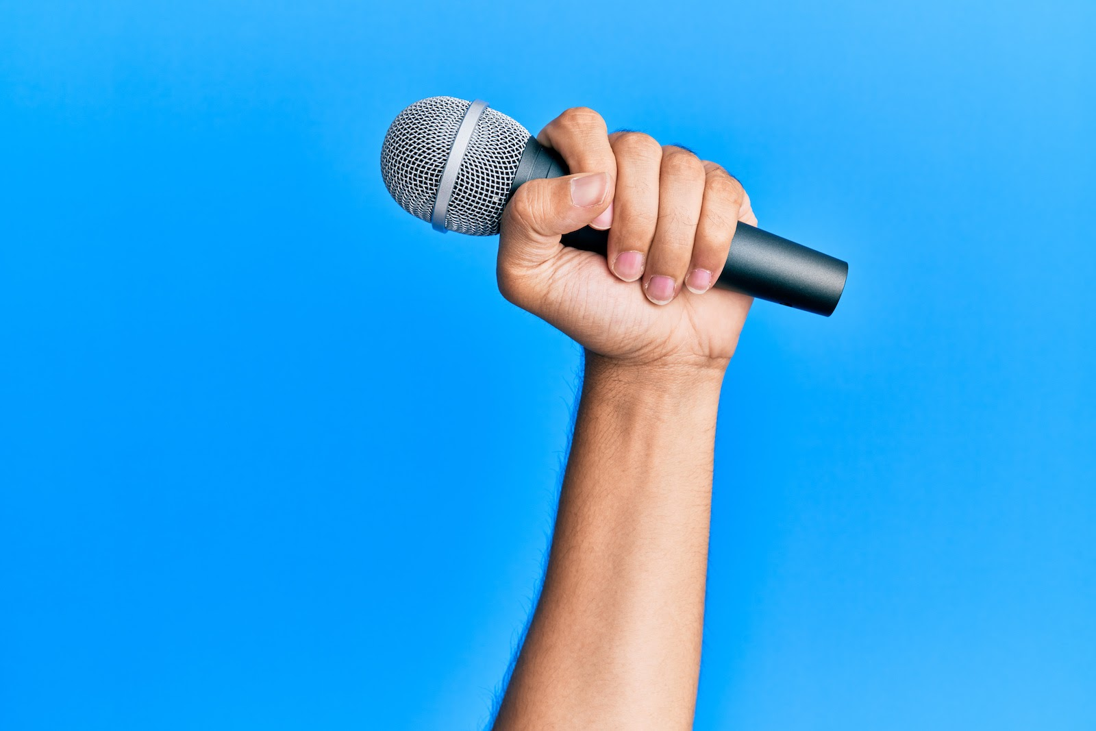 How to host a webinar: A person holds a microphone to present at a webinar
