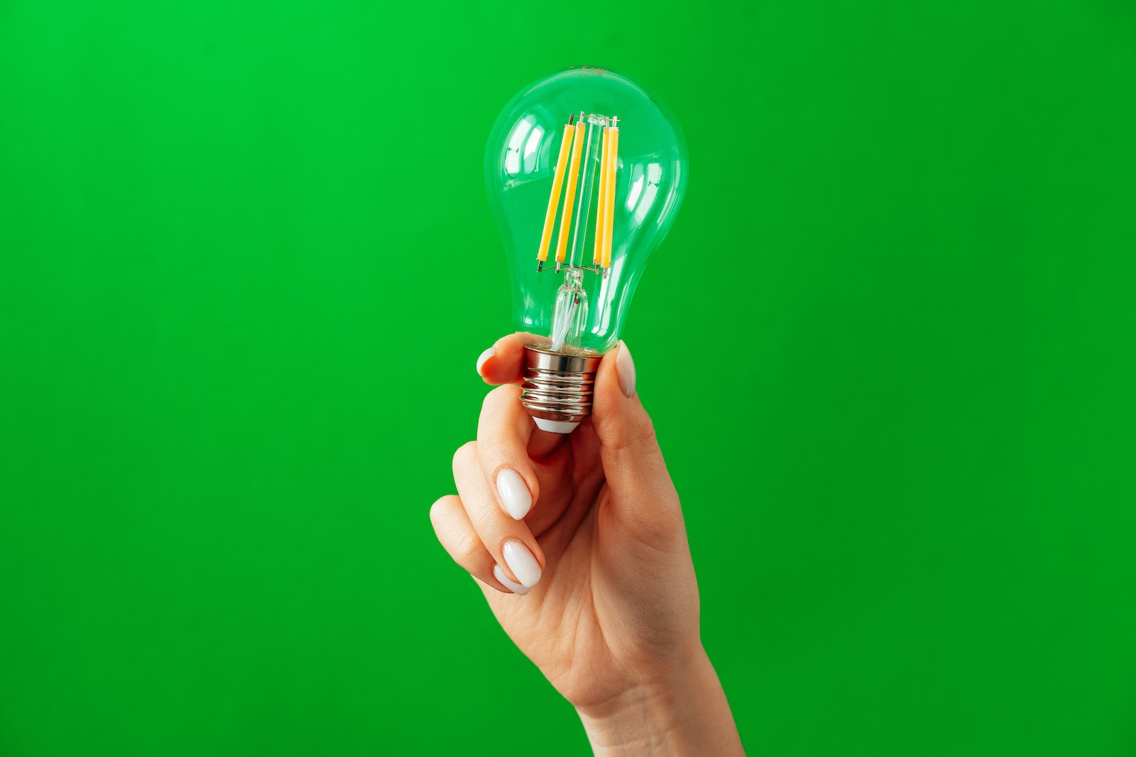 A hand holds a light bulb to represent planning a virtual trade show
