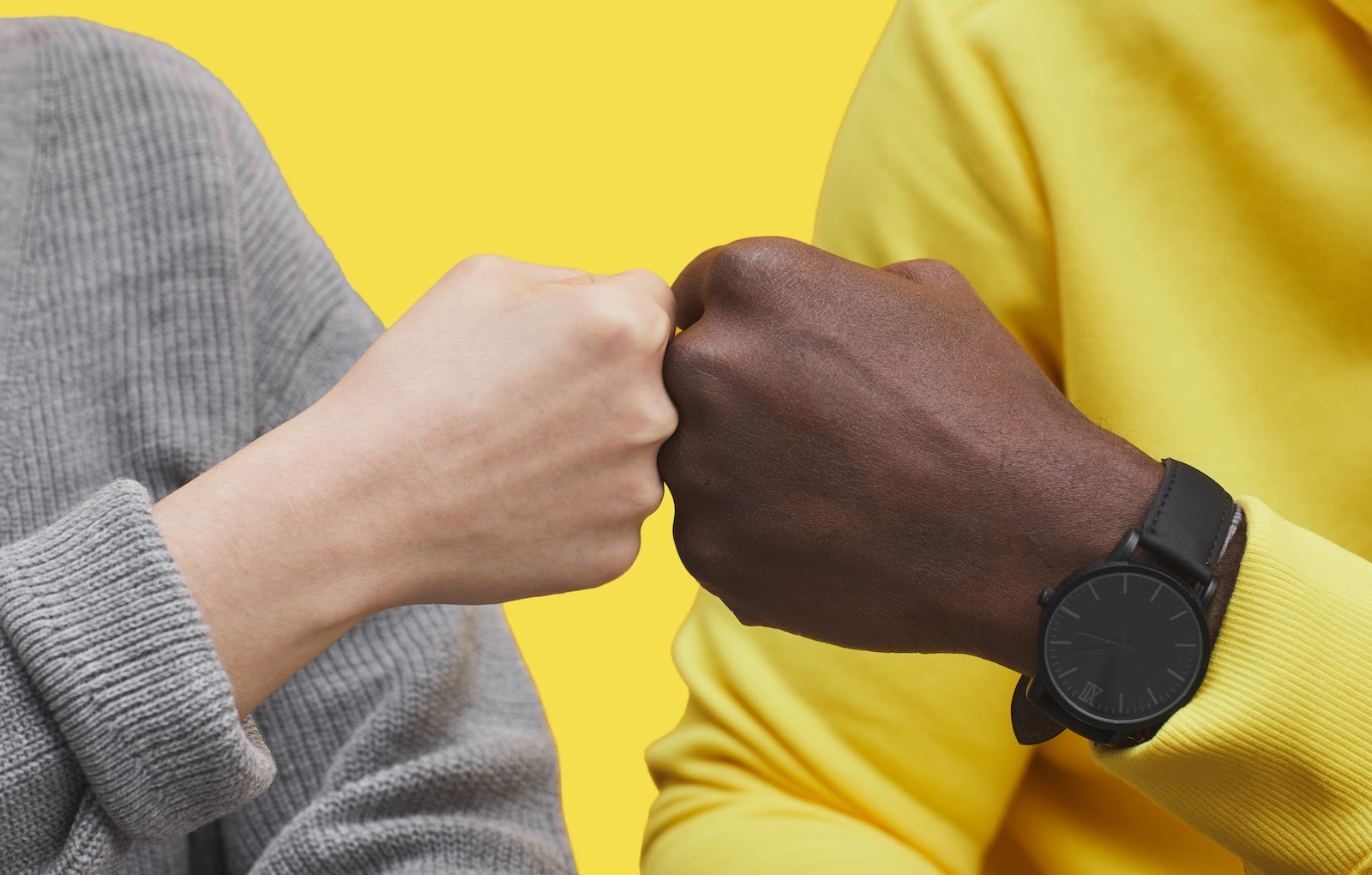 A man and woman fist bump to celebrate closing a virtual sales prospect