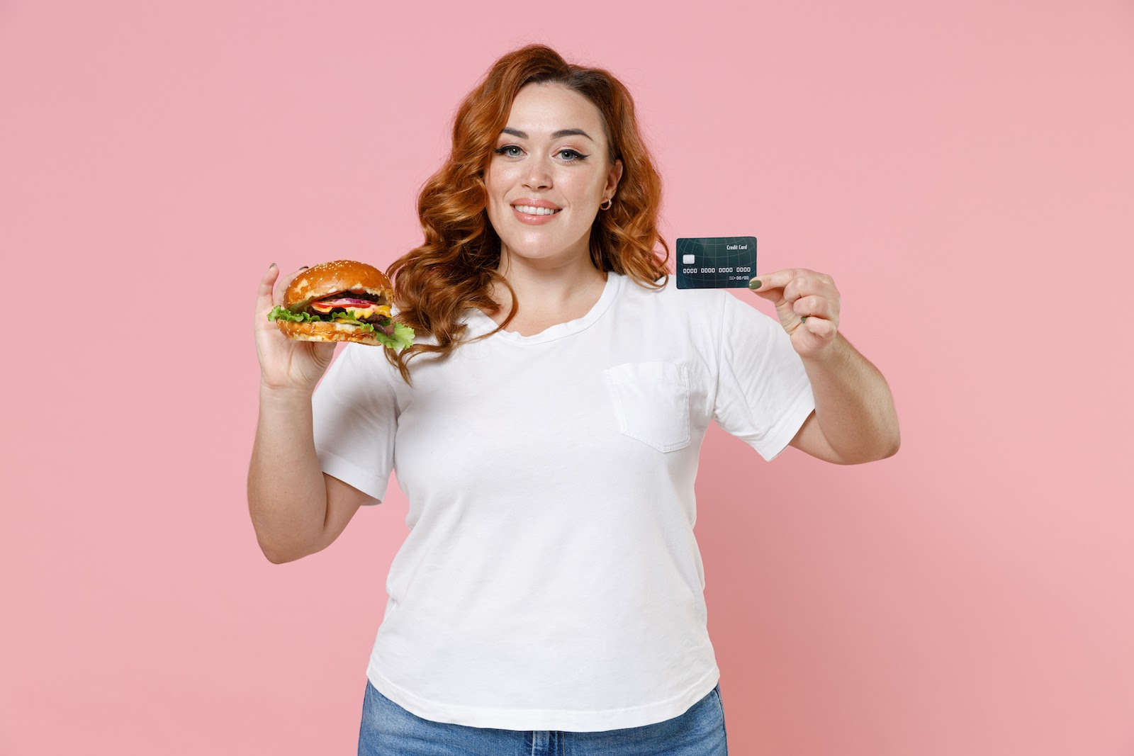 Virtual catering ideas: A woman holds a burger she bought with a virtual credit card