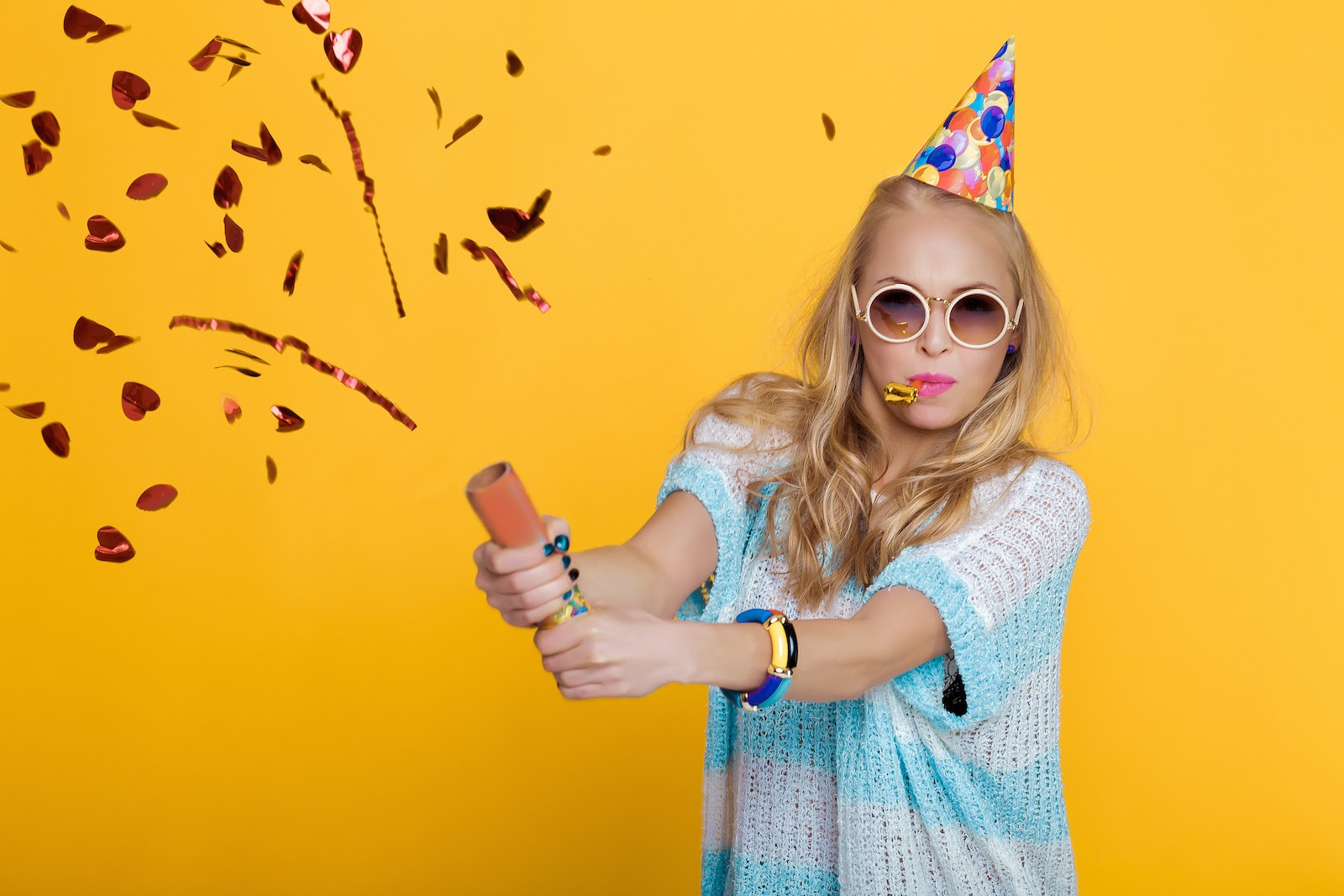 A woman wears a party hat and pops a confetti can as part of the audience engagement at a virtual party