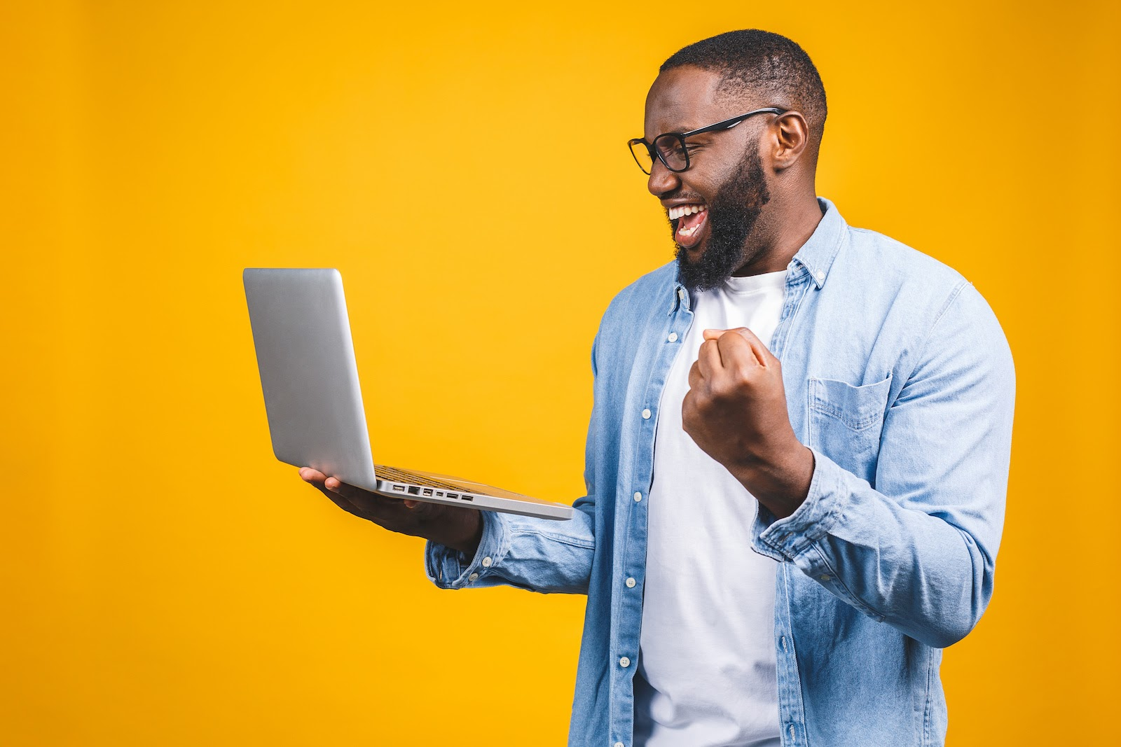 A man is excited about Kudos he got while working on his laptop with remote work software