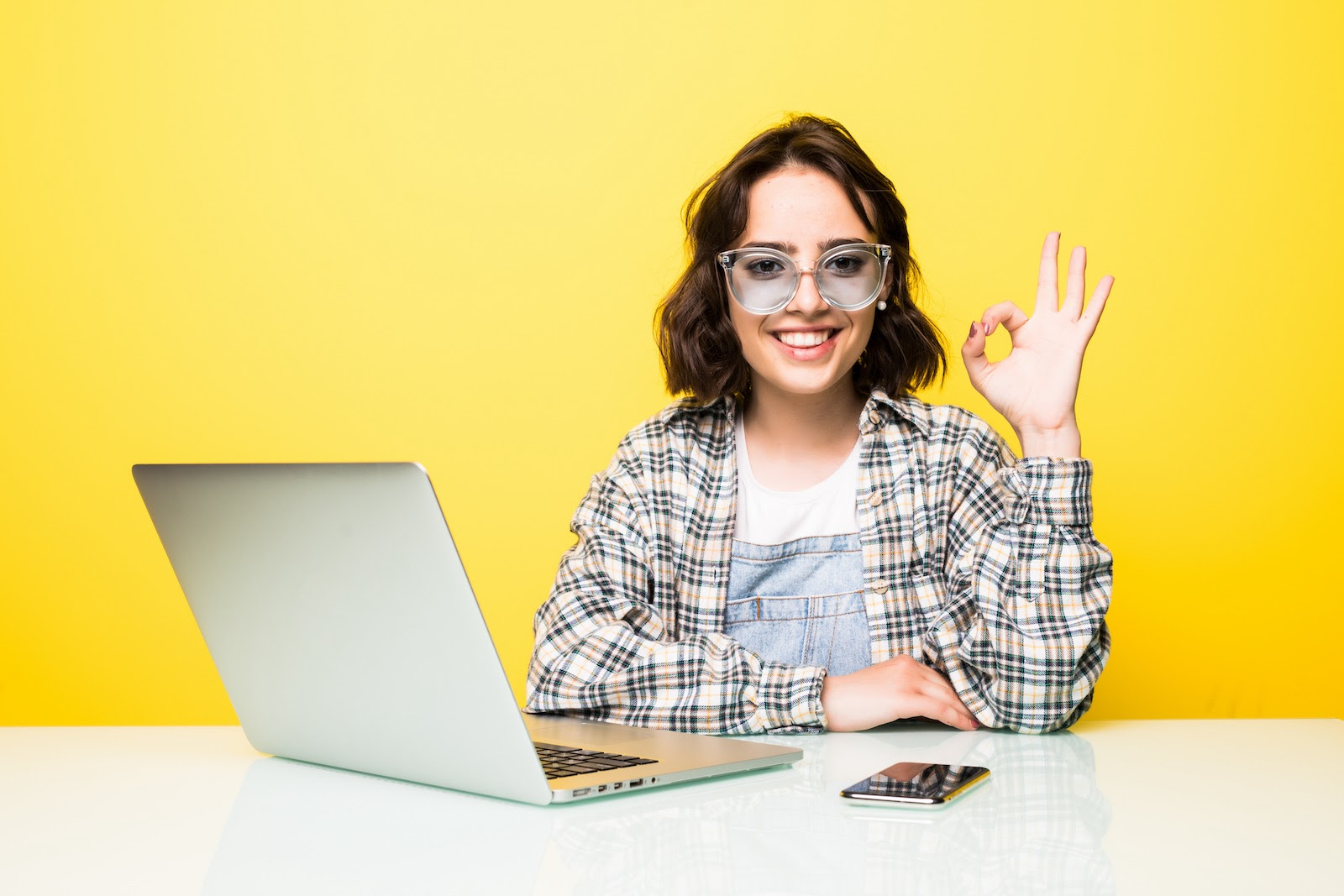 A woman gestures OK while using remote work software on her laptop