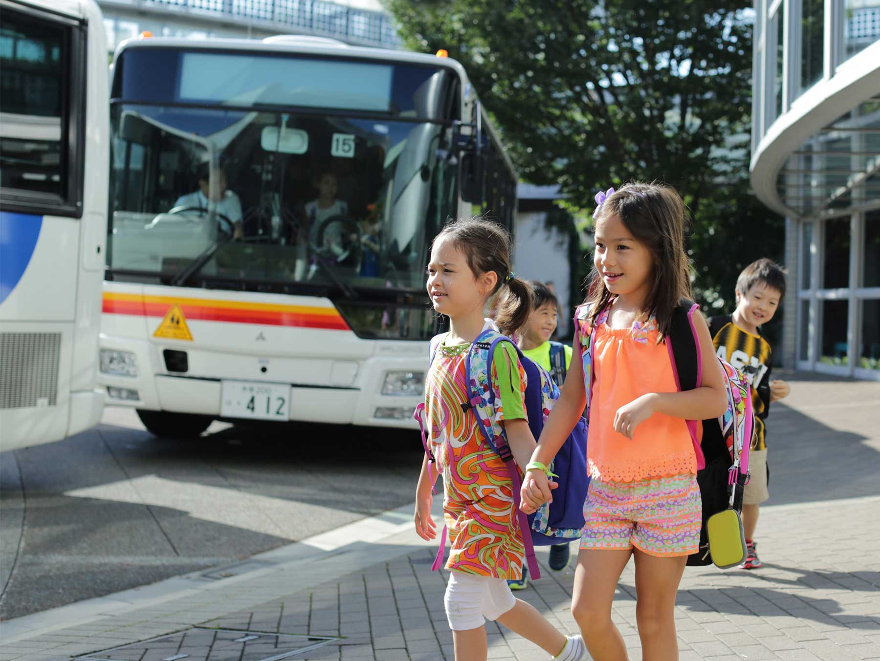 Two Elementary School Girls Walk Off Their Bus Hand-in-Hand