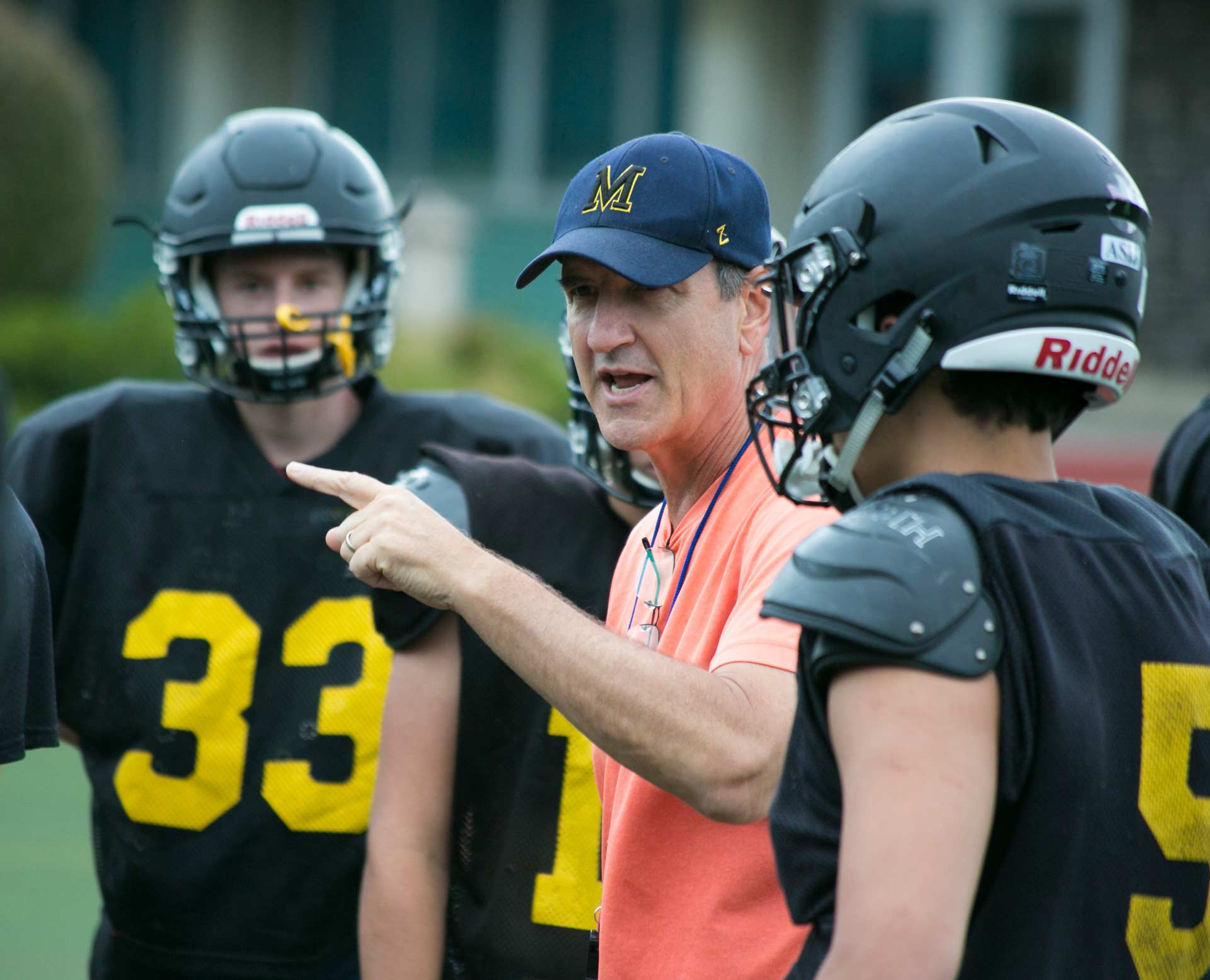 A Football Coach Talks to Geared-Up Players at Practice