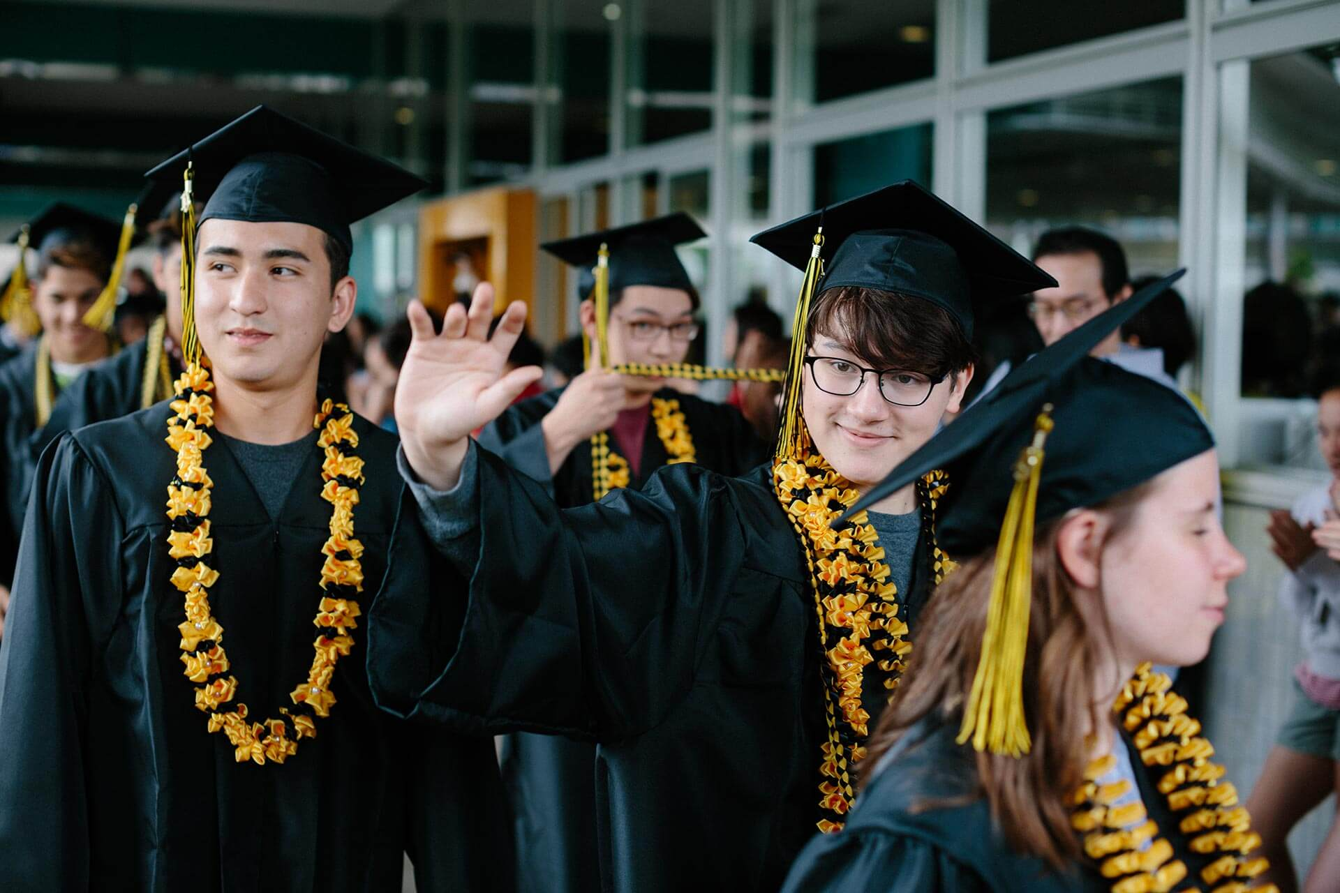 A High School Student in Cap and Gown Waves During the Senior Walk