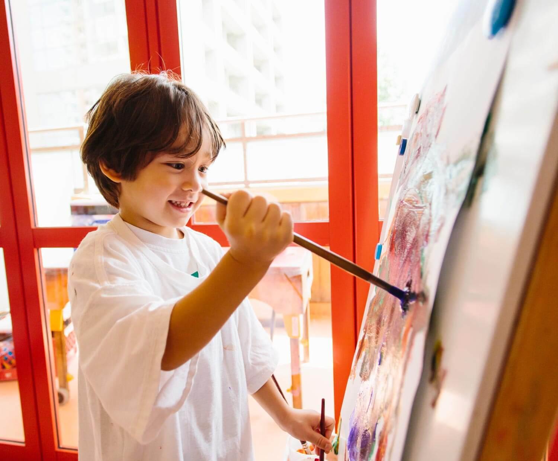 A Kindergarten Boy Paints on a Easel