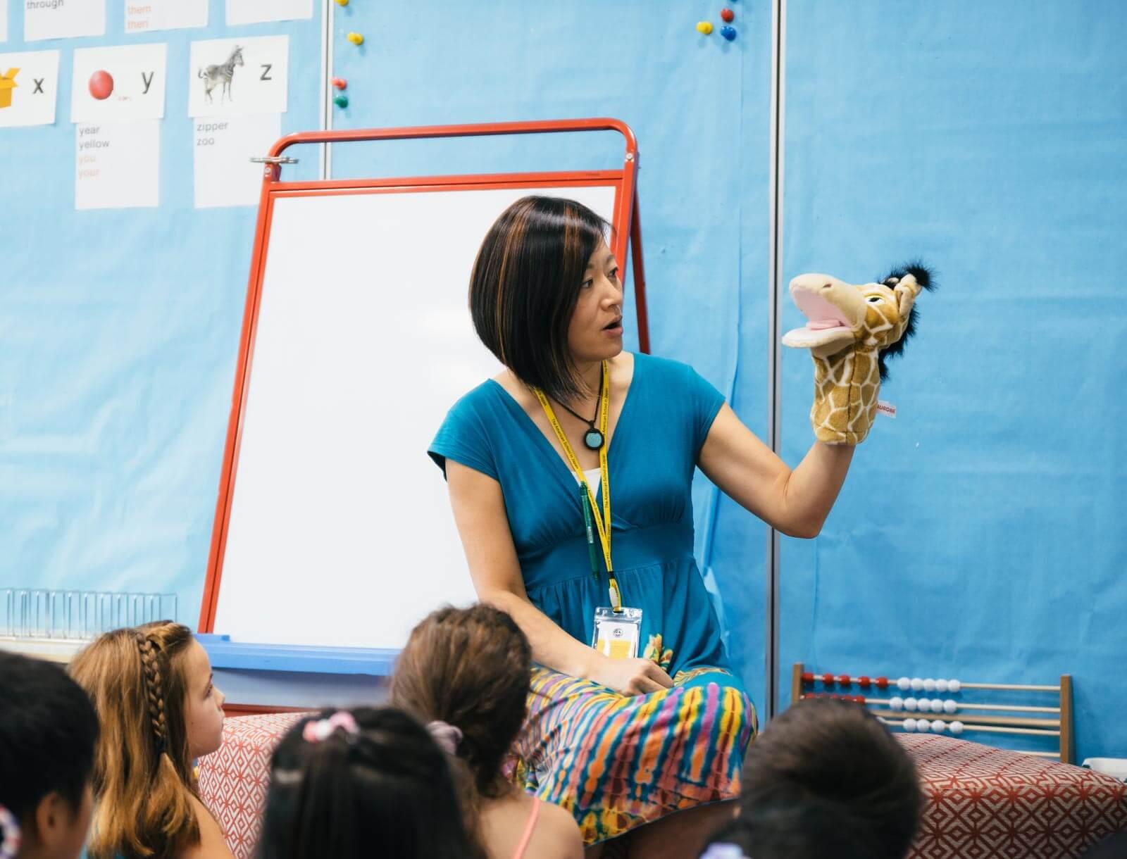 A Teacher with a Giraffe Puppet Tells Elementary School Students a Story