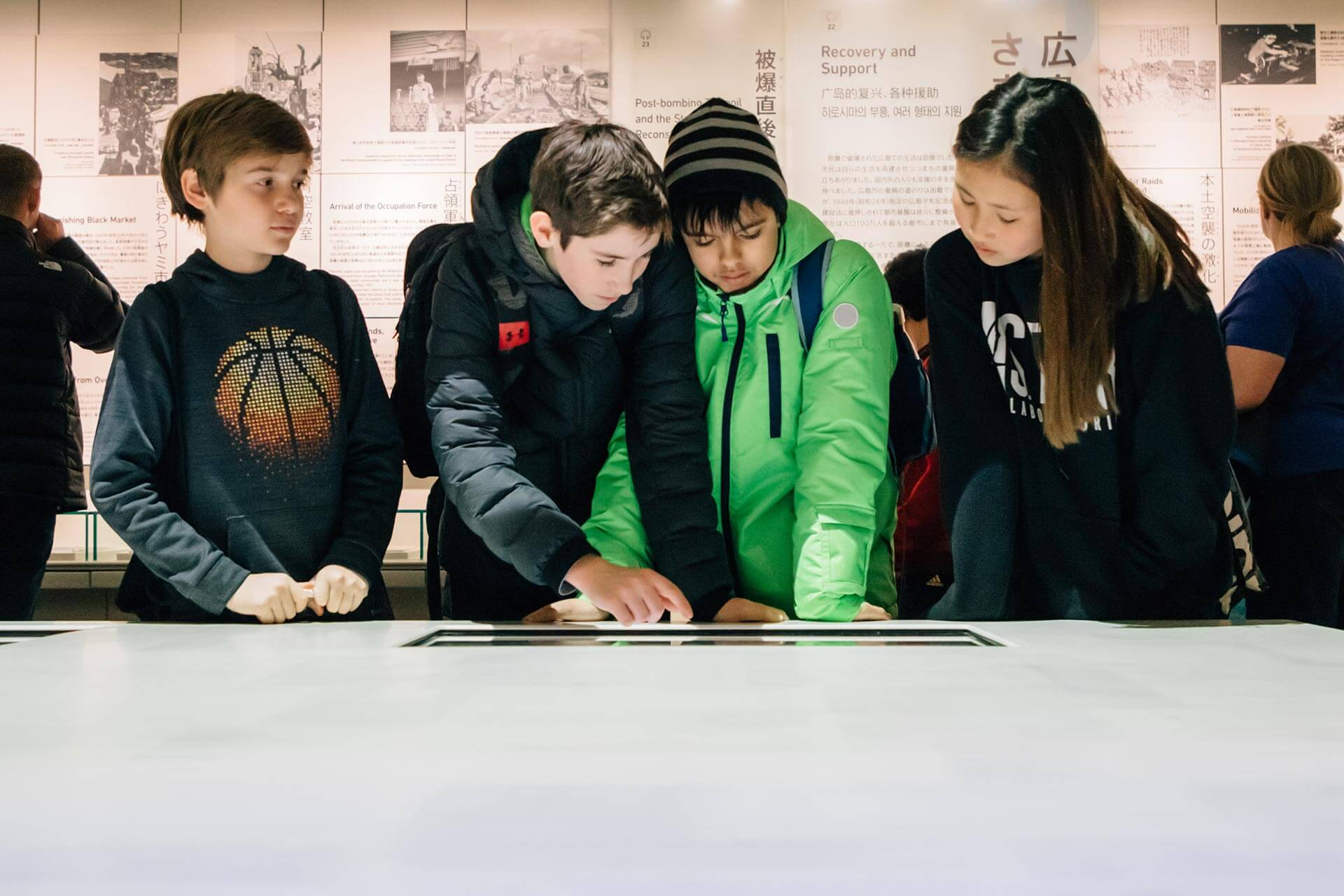 Four Middle Schoolers Use an Interactive Surface at the Hiroshima Peace Museum