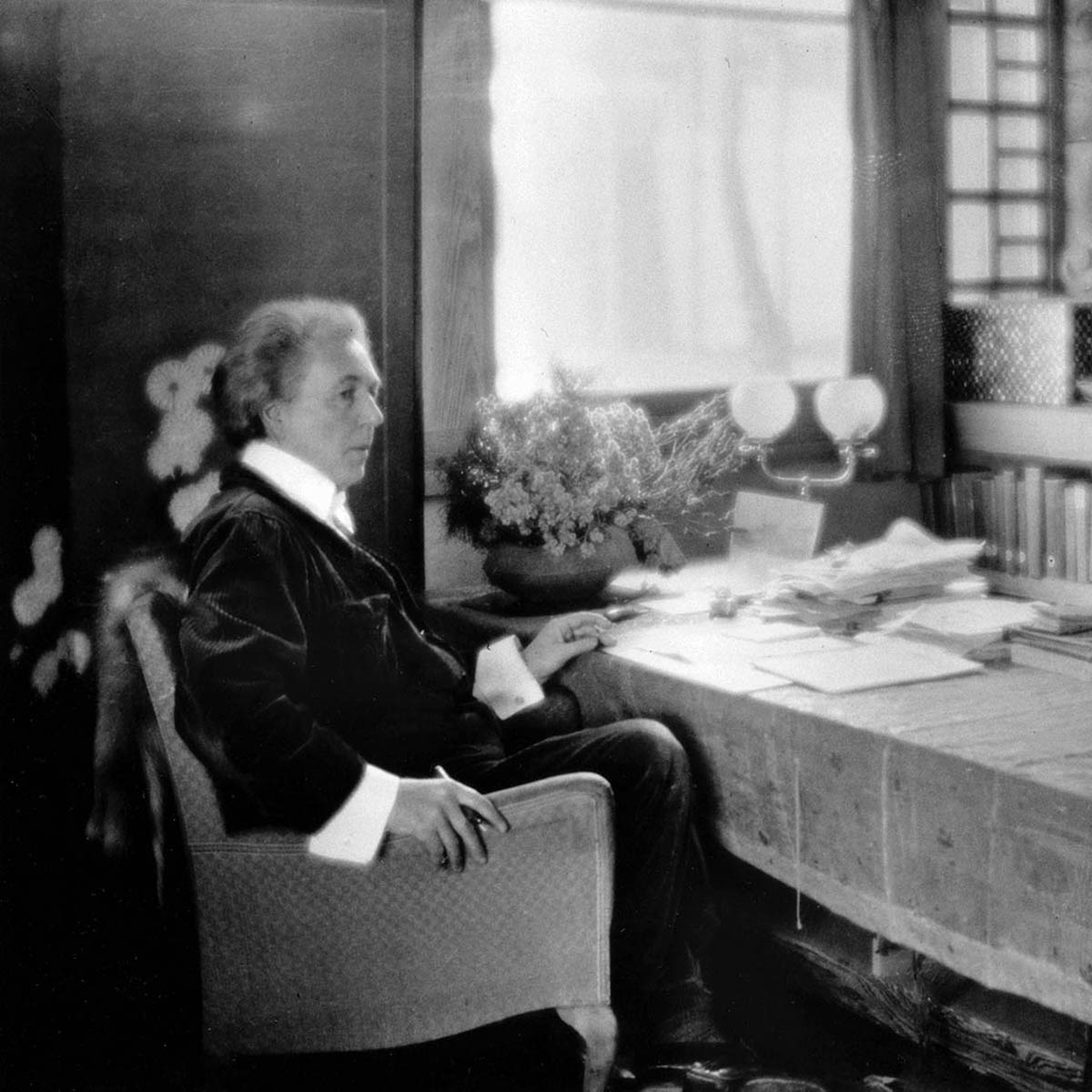Frank Lloyd Wright Sits at a Table