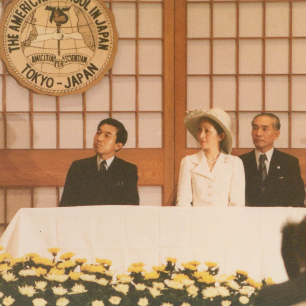 Crown Prince Akihito and His Wife Sit at a Table During ASIJ's 75 Anniversary Celebration