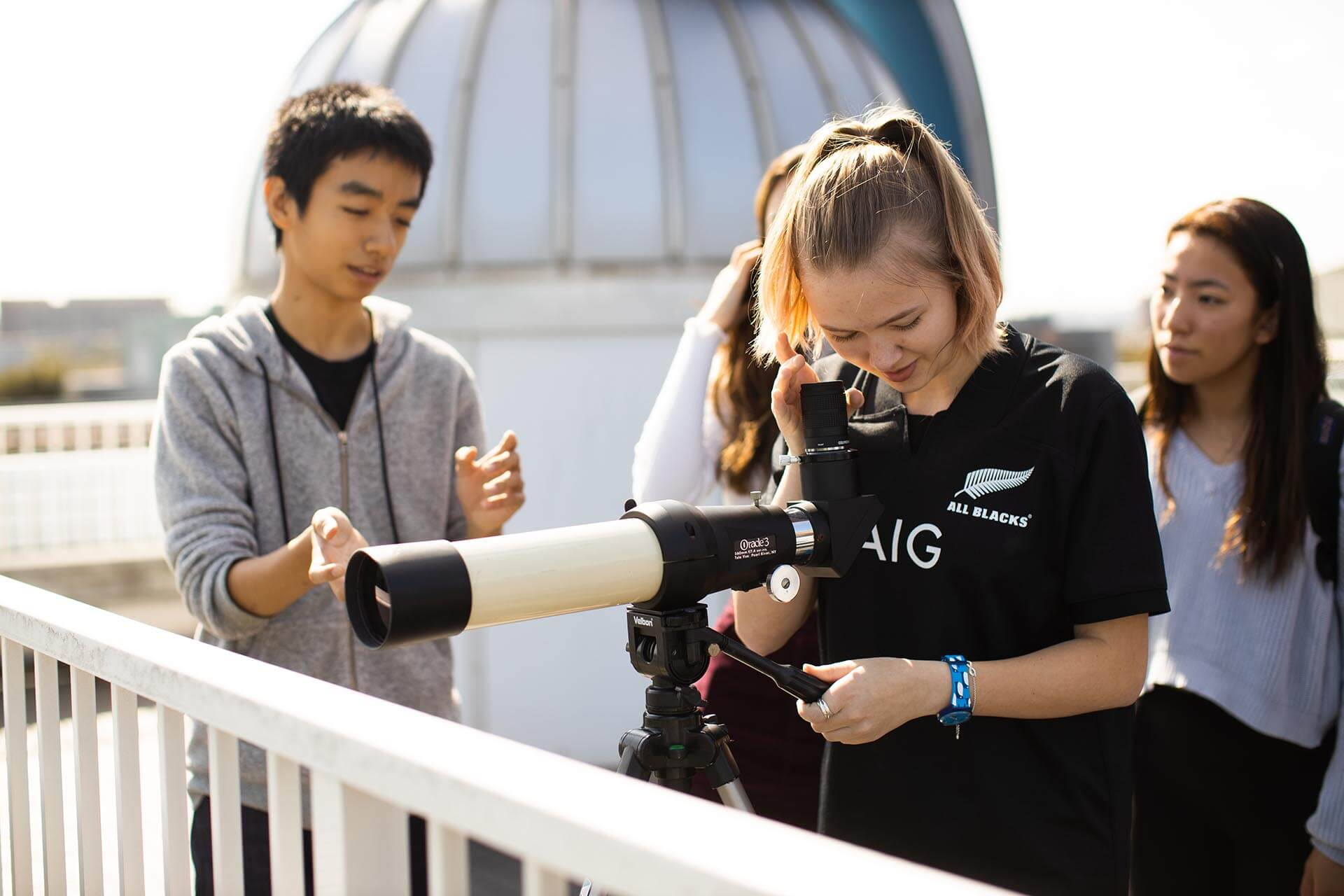 a Student Looks Through a Telescope on a School Rooftop