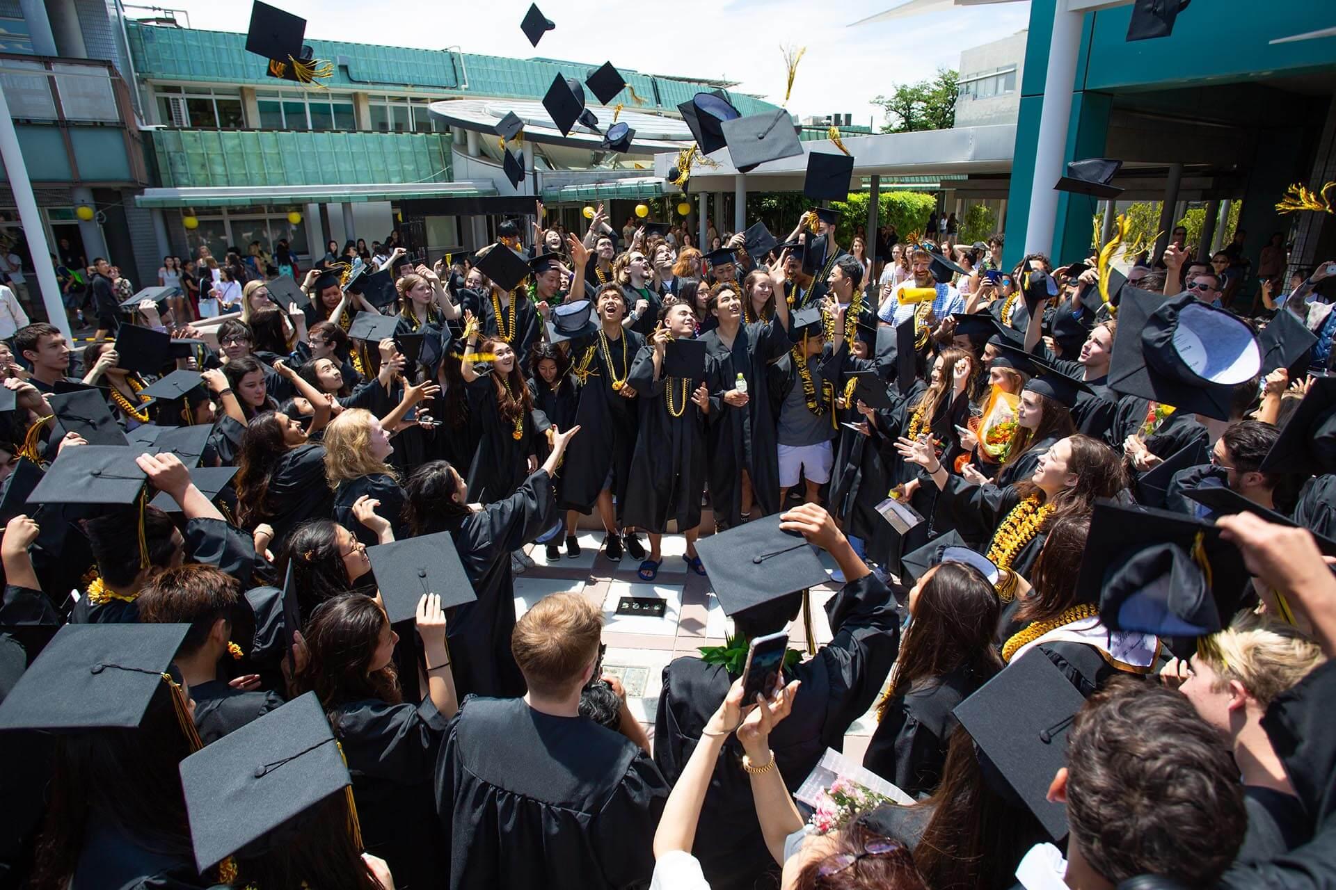 High School Graduates Toss their Caps in the Courtyard