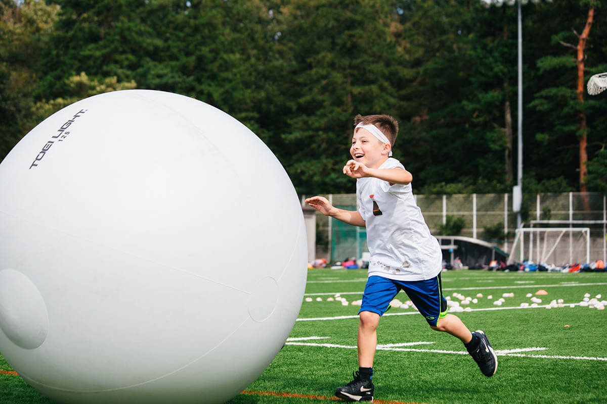 An Elementary School Student Runs with a Giant Ball During a Relay