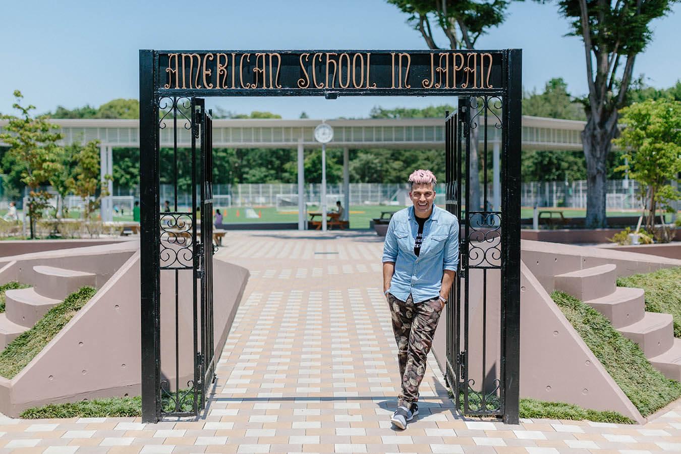 Alum Bobak Ferdowski poses next to the historic ASIJ Gate on visit