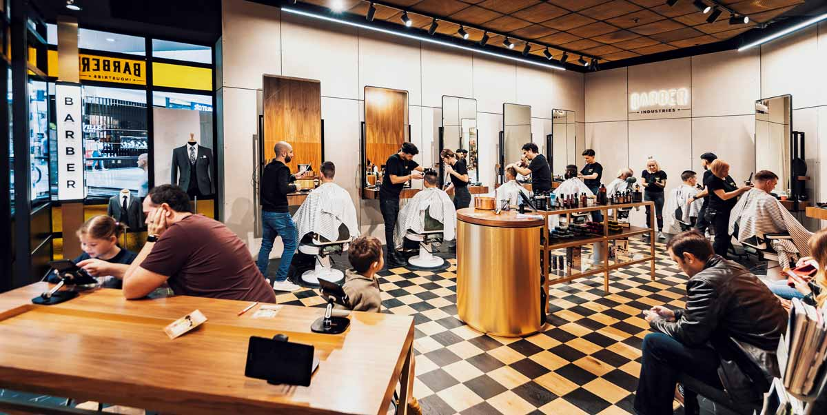 People waiting for hair cuts in the barbershop at Barber Industries Kotara