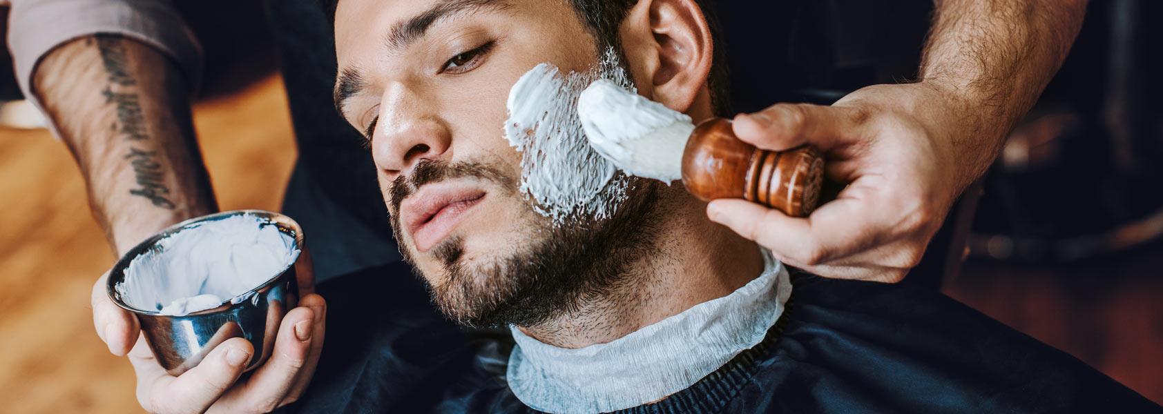 Barber Applying Shaving Cream To Customer Face