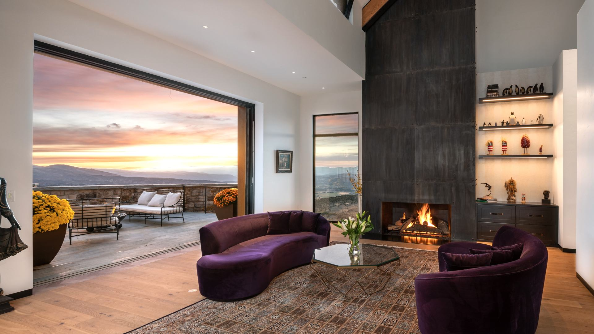 Modern living room with outdoor patio overlooking mountains.