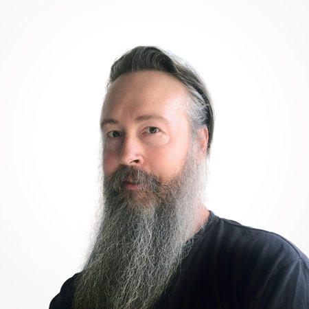 Middle-aged man with a long grey beard partially smiling, while wearing a black shirt