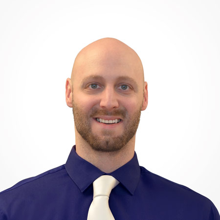 Young bald businessman with a beard wearing a dark blue dress shirt with a white tie