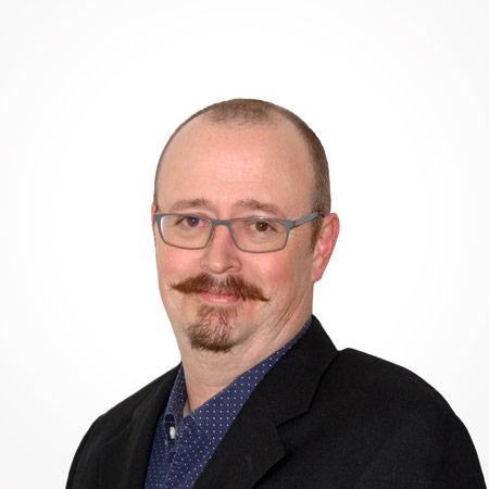 Middle-aged balding white businessman wearing a black dress jacket