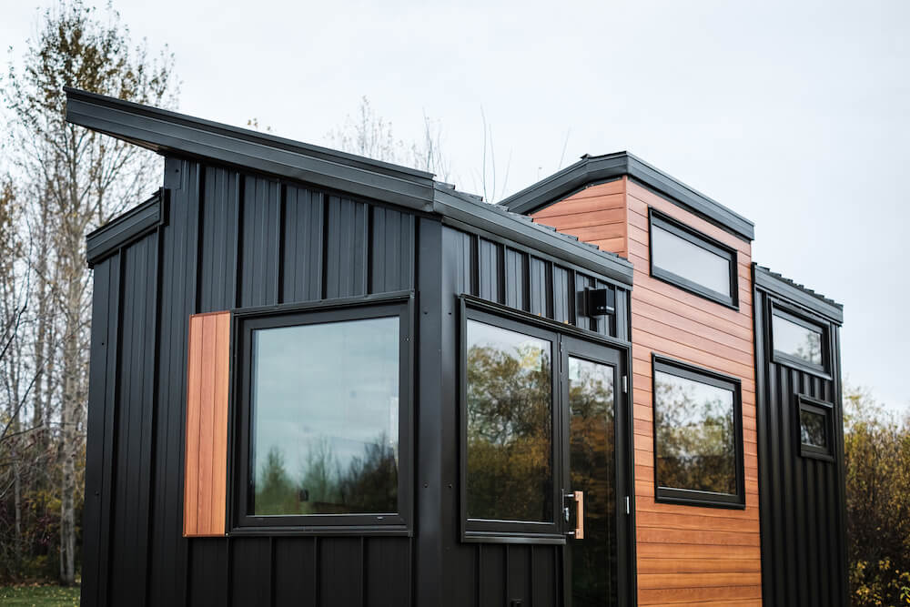 Exterior of a modern tiny house with black and wood siding