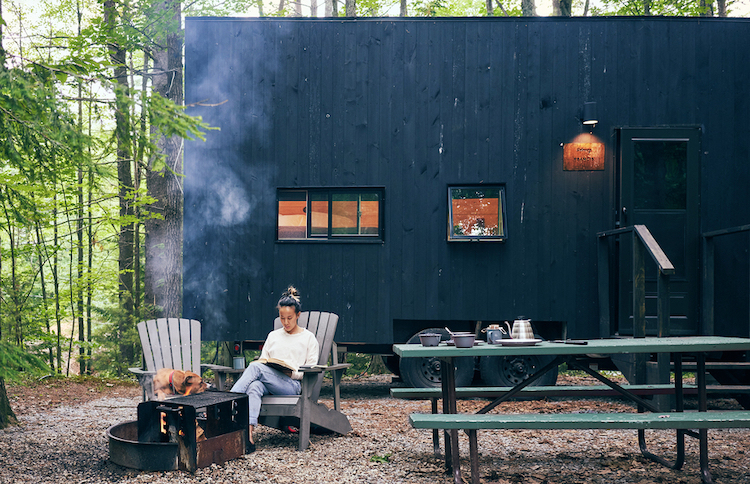 Lady reading book near fire and Getaway Tiny House
