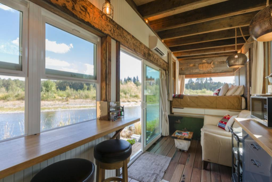 Living room looking out tiny home on lake